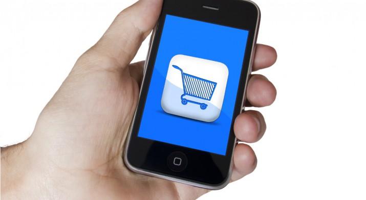 A mão de um pessoa segurando um celular e na tela do celular aparece um carrinho de compras, demonstrando o e-commerce mobile