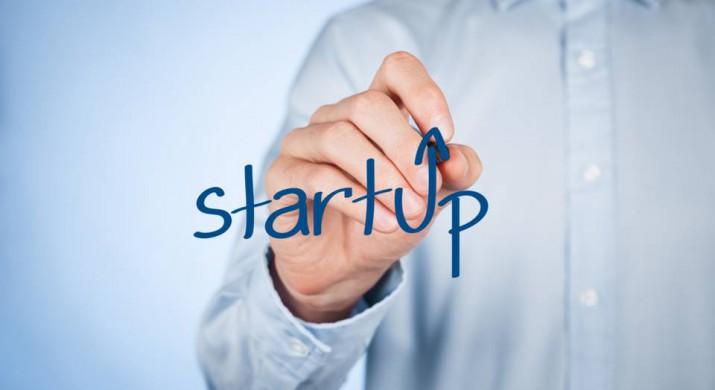 """Homem engravatado escreve o nome """"startup"""", representando essa nova forma de fazer negócios"""