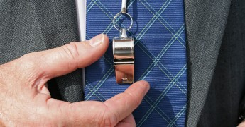 Businessman's' tie and shirt shown with a silver whistle resting on the tie