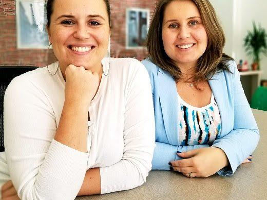 Duas mulheres jovens, irmãs, sentadas em uma mesa de escritório. Elas começaram uma franquia de intercâmbio e turismo