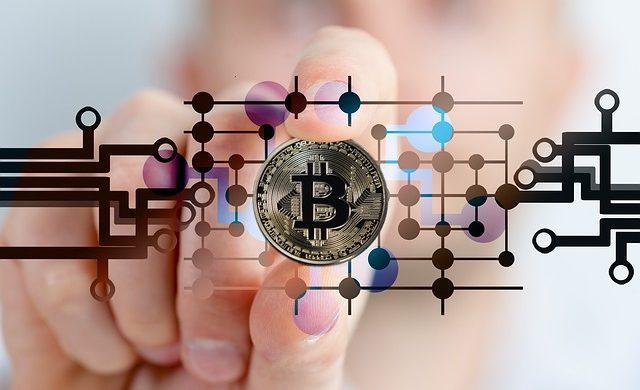 "Moeda grande centralizada na foto e dentro dela escrita a letra ""b"" em maiúscula, representando a moeda Bitcoin"