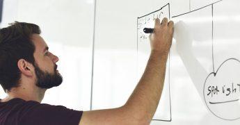 Rapaz jovem escrevendo em um quadro branco, passando dicas sobre como uma startup fez seu primeiro milhão