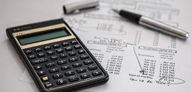 Calculadora e uma caneta em cima de papéis