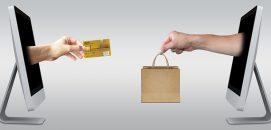 Dois computadores, um de frente para o outro, trocando uma sacola de compras por um cartão de crédito, representando o ecommerce