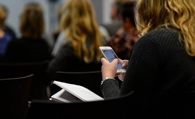 Mulher jovem usando o celular, referência a como as marcas usam os aplicativos