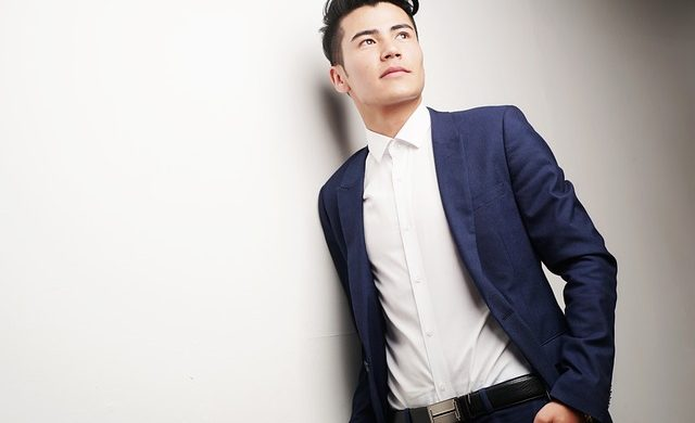 Executivo jovem encostado na parede com o olhar distante pensando nos desafios da carreira