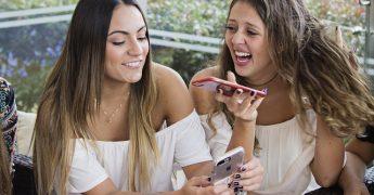 Duas meninas jovens com celulares nas mãos, atuando como influenciadoras digitais, nova tendência do marketing