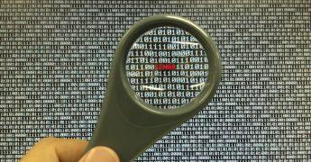 Uma lupa em cima de várias numerações muito juntas, representando análise de dados, investigação e trabalho das agências de inteligência