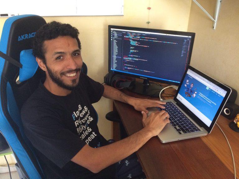 O freelancer Mario Ernesto sentado na mesa na frente de seu computador desempenhando a função de freelancer, através de uma plataforma