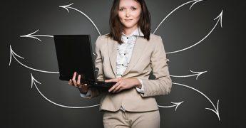 Mulher executiva com computador na mão resolvendo várias questões, representando as diversas plataformas que ajudam a reducir gastos corporativos