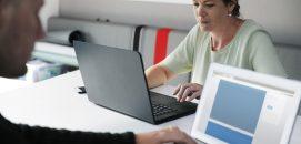 Mulher na frente de um computador, sugerindo que está administrando um pequeno negócio