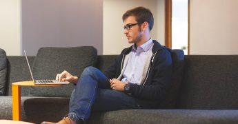 Homem jovem sentado em um sofá, mexendo no computador, representando um jovem empreendedor
