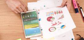 Papéis espalhados pela mesa com gráficos e um celular com aplicativos, representando a organização das finanças