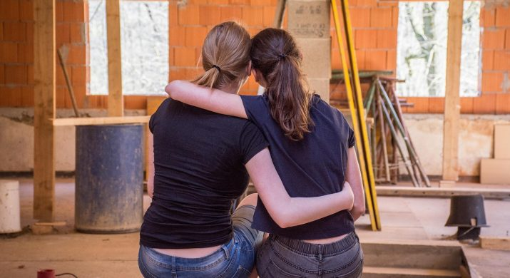 duas mulheres jovens abraçadas diante de uma sala em construção, representando cooperação