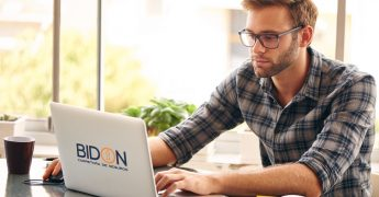 Homem jovem traballhando em um computador, representando um home office