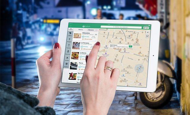 Mãos femininas mexendo em um ipad, representando um aplicativo para facilitar a entrega de produtos