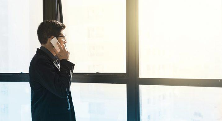 Homem falando ao celular a beira da janela, representando um executivo brasileiro
