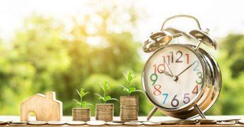 Relógio despertador em estilo mais antigo, moedas ao lado dele, e dentro das moedas está crescendo plantas pequenas, demonstrando tempo e dinheiro