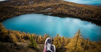 Um lago envolto de uma linda vegetação e na parte baixa da imagem, aparecem dois pés cruzados, sugerindo que alguém está tranquilamente descansando e admirando a paisagem