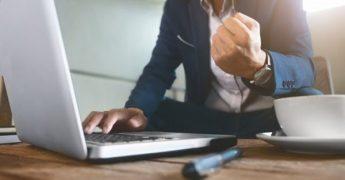Empresário em uma mesa na frente do computador, fazendo um gesto vibrante com o punho fechado