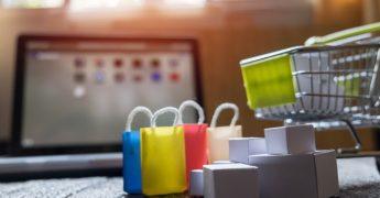 Carrinho com várias sacolinhas ao lado e ao fundo da foto, meio desfocado, um computador, representando uma loja virtual