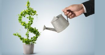 Uma mão segurando um regador e molhando uma planta que tem o formato de um cifrão, representando boas oportunidades de negócios no franchising