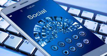 Celular e teclado de computador. No celular, tem várias opções para conectar às mídias sociais