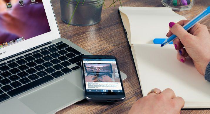 Mãos femininas escrevendo em um caderno com celular e computador ao lado, representando a gestão de um negócio