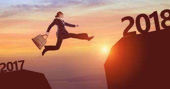 Uma mulher pulando do topo de um morro a outro, com o pôr do sol ao funto e cada morro representando o ano de 2017 e 2018