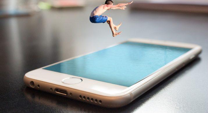 Menino pulando em uma piscina, só que a piscina é representada por um smart phone, representando o comércio eletrônico no verão