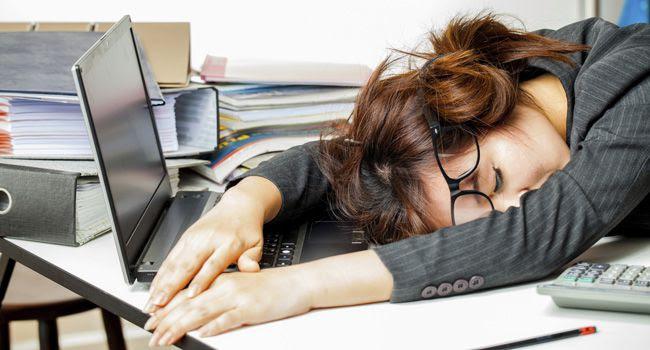 Mulher jovem dormindo em cima do teclado do computador, representando a procrastinação no trabalho