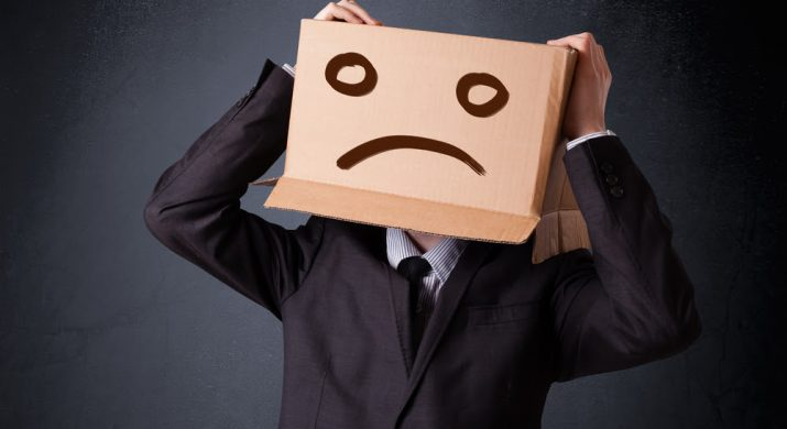 Um executivo de terno com uma caixa de papelão na cabeça. Na caixa tem o rascunho de um desenho de um cara triste, representando erros na estratégia de marketing da empresa