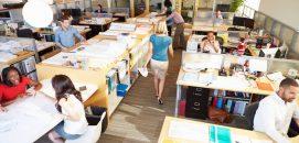 Espaço de coworking com pessoas trabalhando em suas mesas e computadores