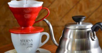 Xícara com filtro de café em cima e bulê do lado, representando a marca Sterna cafe