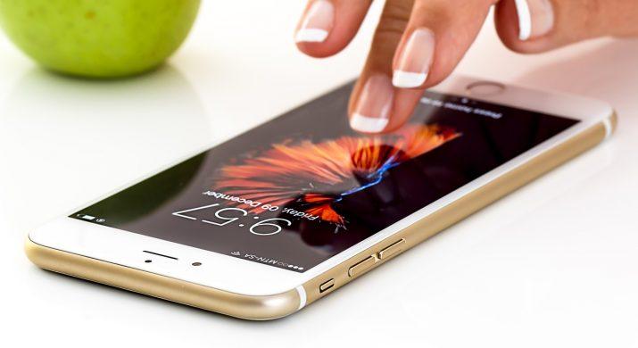 Mãos femininas usando os aplicativos do telefone