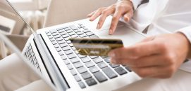Mão em um teclado de computador e a outra segurando um cartão de crédito, representando o e-commerce