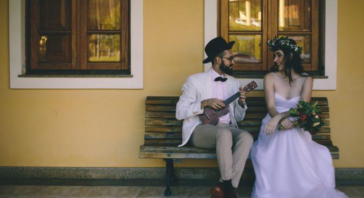 Casal sentado em um banco, ela de vestido de noiva e ele de roupa esporte-social, representando um ecommerce de vestidos de noiva despojados